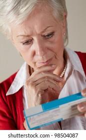 Senior woman looking at prescription drug pack