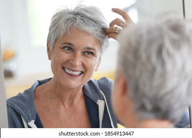 senior woman looking at that white hair in a mirror