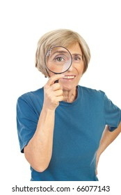 Senior woman looking through magnifying glass and smiling isolated on white background