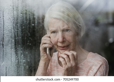 Senior woman is looking worriedly out of the window of her home while talking to someone on the phone.