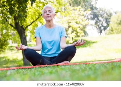 Senior woman in lotus pose sitting on green grass at summar day