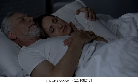 Senior woman lying on male chest, couple sleeping in bed, man hugging her