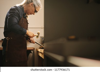 Senior woman making jewelry using traditional tools in her workshop. Female goldsmith wearing leather apron and glasses making a ring at a workbench using hammer and steel sizing tool.