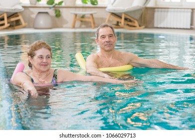 senior woman and man doing aqua fitness with swim noodles.