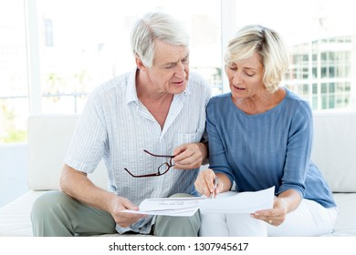 senior woman and man doing home finance together on sofa