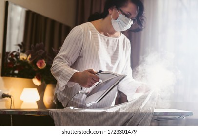 Senior woman in medical mask is ironing clothes using steam. Steaming washed laundry. Self-isolation and quarantine for the elderly during the Covid-19 coronavirus pandemic.