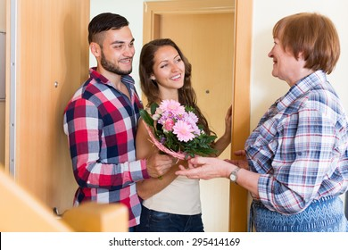 Senior woman meeting  smiling young couple with flowers at the door