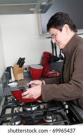 Senior woman in a modern kitchen cooking a meal.