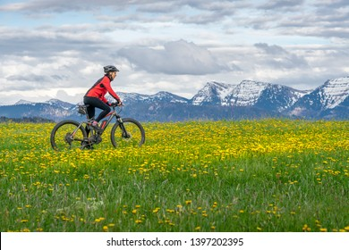 senior woman mountainbiking on a e-mountainbike in early spring, in the Allgaeu Area, a part of the bavarian alps,Germany