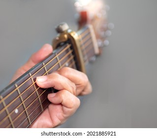 Senior woman musician hand holds classic wooden guitar neck. Old female guitarist put fingers on acoustic guitar fingerboard playing C chord sound D key as capo on fret 2. String musical instrument