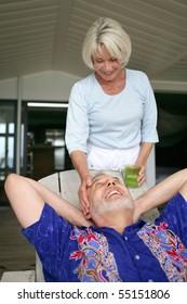 A senior woman next to a senior man resting in a deck chair