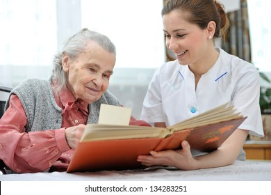 Senior woman and nurse looking together at album with old photographs