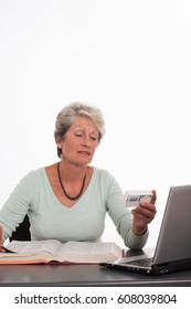 senior woman on her computer with a book and a box of drugs