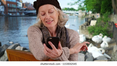 Senior woman on park bench by river in Windsor looking at cell phone with swans
