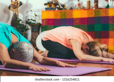 Senior woman on private yoga class with personal trainer.