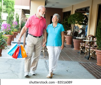 Senior woman on a shopping spree looks up at her handsome husband who's carrying her bags.