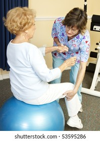 Senior woman on yoga ball, working with a physical therapist.