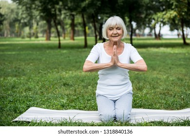 senior woman on yoga mat in meditation sukhasana sitting pose with folded hands