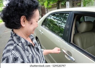 senior woman open car door
