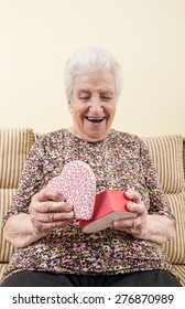senior woman opening a gift box