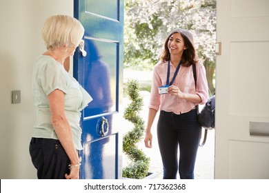 Senior woman opens door to female care worker showing her ID