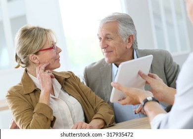 Senior woman at optical store choosing eyeglasses