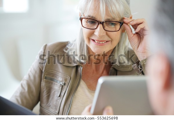 Senior woman in optical store trying eyeglasses on