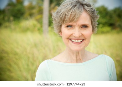 Senior woman outdoors in countryside smiling at camera