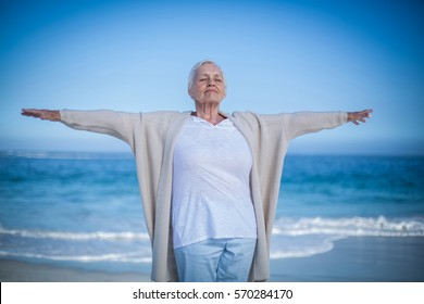 Senior woman outstretching arms at the beach