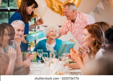 Senior woman is overwhelmed with emotion as she is surprised with a birthday party by her friends and family.