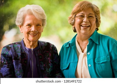 Senior woman with an oxygen nose hose (cannula) and a mature women smile as they pose for a portrait together.