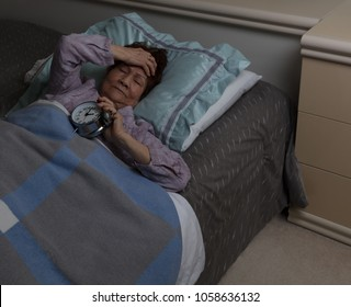 senior woman with painful headache holding her alarm clock during nighttime