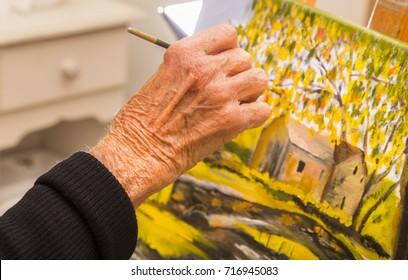 Senior woman painting, closeup of hand holding brush