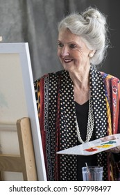 Senior woman painting at an easel in a studio