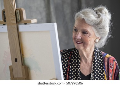 Senior woman painting at an easel in a studio, close up shot