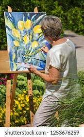 Senior woman painting flowers on canvas in garden during sunny day.