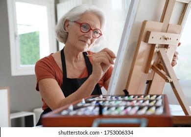 Femme aînée peignant sur toile