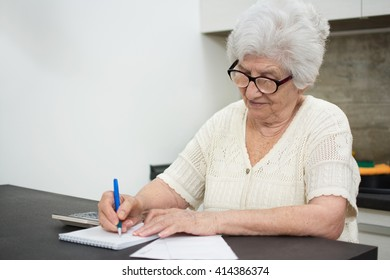 Senior woman with papers or bills and calculator writing at home.