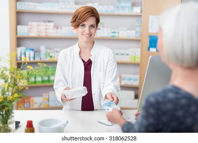 Senior woman patient paying for her medication in a pharmacy handing the pretty smiling female pharmacist a banknote