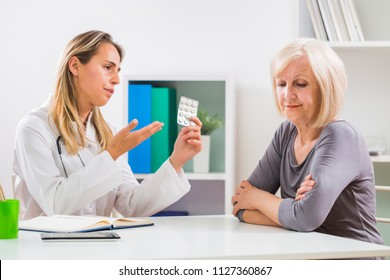 Senior woman patient refusing to take pills for her health problems.