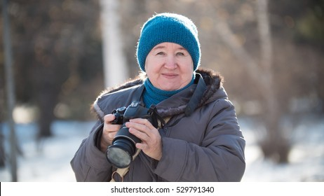 Senior woman with photo camera at winter day, outdoor