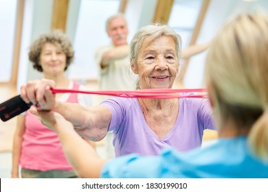 Senior woman in physiotherapy class with trainer doing exercise with the elastic band