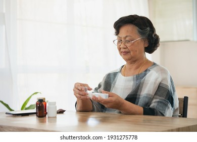 Senior woman picking medication from medicine bag put in a daily pill organizer box and closing the lids. Old woman taking care herself for health. Health and Medical concept.