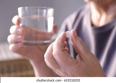 Senior woman with pill and glass of water at home, closeup