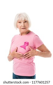senior woman with pink ribbon touching breast and looking at camera isolated on white, cancer concept