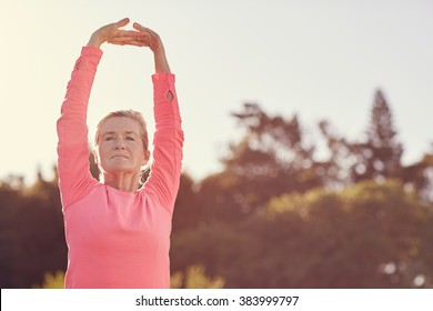 Senior woman in a pink sporty long-sleeved top stretching her arms above her head to warm-up for some early morning exercise with gentle sunflare behind her