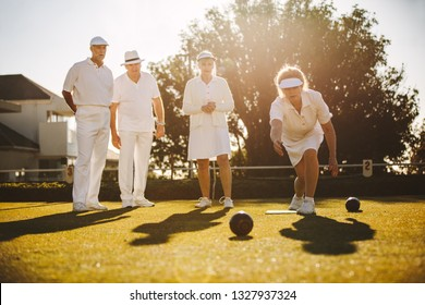 Senior woman playing boules with her friends standing in the background. Woman bending forward to throw a boules in a park.