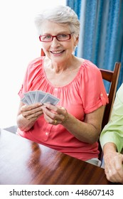 Senior woman playing cards in a retirement home