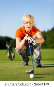 Senior woman playing golf looking and aiming for the hole