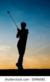 Senior woman playing golf - pictured as a silhouette against an evening sky